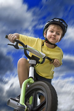 child cyclist wearing a bicycle helmet