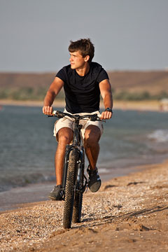 bicycle rider, riding along a beach