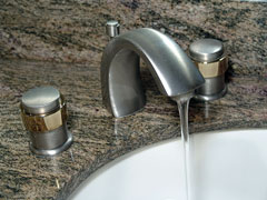 brushed nickel bathroom faucet on granite countertop with undermount porcelain sink