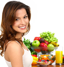 smiling woman with healthy fruits and vegetables