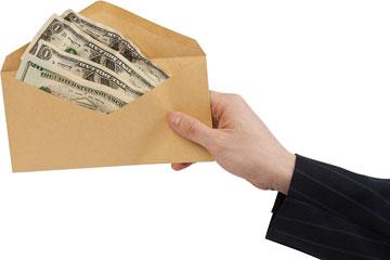 a hand proffering a cash advance envelope