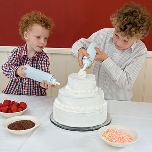 two children decorating a cake