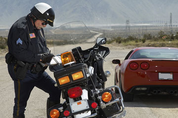 a motorcycle traffic cop writing a speeding ticket