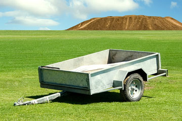 an empty utility trailer parked on a green meadow