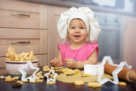 little girl chef baking cookies in a kitchen