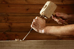 carpenter using a wood mallet and a chisel
