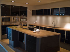 modern kitchen with stainless steel appliances, black cabinets, and wood countertops